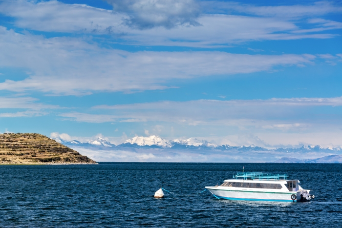 View of a boat on Lake Titicaca with Andes mountains in the background as seen from Isla del Sol in Bolivia