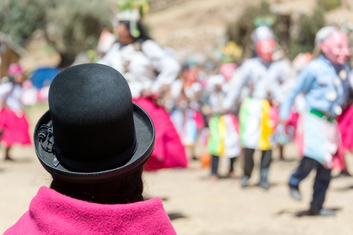 Indigenous woman in traditional clothes watching a traditional dance on Island of the Sun on the Bolivian side of Lake Titicaca