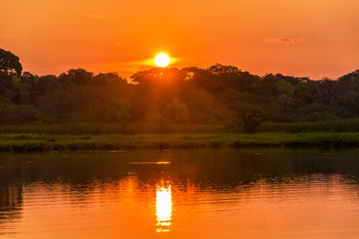 Red and orange sunset over a lake in Madidi National Park in Bolivia