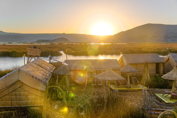 Sunset with strong lens flare over the Uros floating islands on Lake Titicaca near Puno, Peru