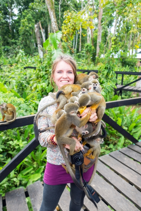 Woman holding approximately ten squirrel monkeys in Leticia, Colombia